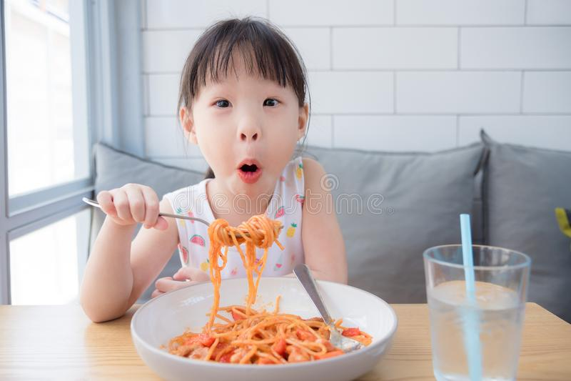 Girl enjoy eating spaghetti on table at restaurant royalty free stock image