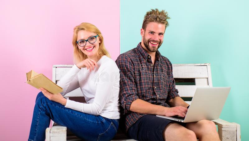 Girl enjoy her life while husband freelancer works with laptop. Woman smiling face reading book near man working. Girl enjoy her life while husband freelancer royalty free stock photos