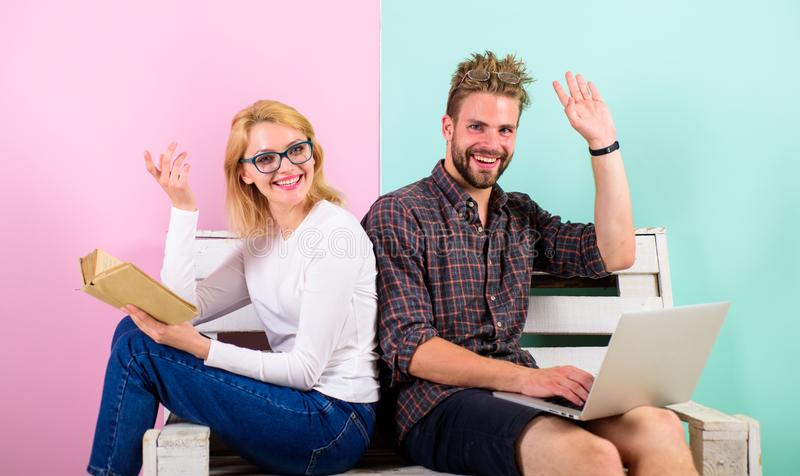 Girl enjoy her life while husband freelancer works with laptop. Woman smiling face reading book near man working. Man. Girl enjoy her life while husband stock photo
