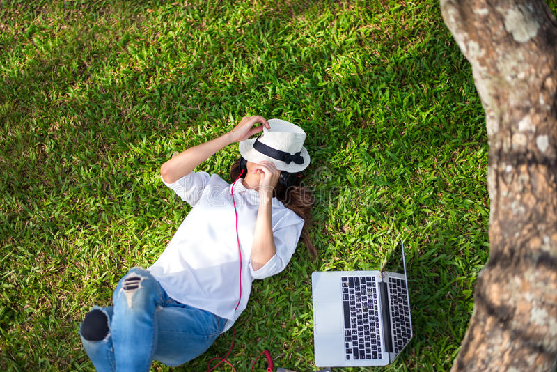 Girl enjoy laying down and play laptop on the grass filed of park in the morning, royalty free stock photo