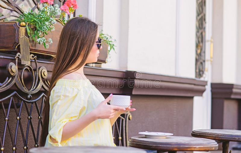 Girl enjoy morning coffee. Waiting for date. Woman in sunglasses drink coffee outdoors. Girl relax in cafe cappuccino stock photography