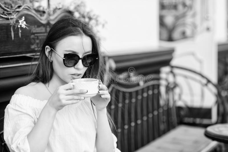 Girl enjoy morning coffee. Woman in sunglasses drink coffee outdoors. Girl relax in cafe cappuccino cup. Caffeine dose royalty free stock photos
