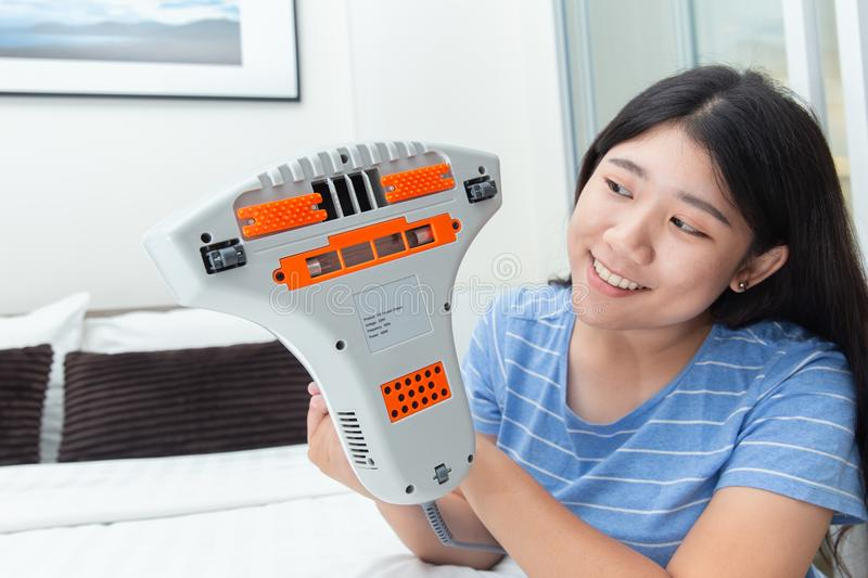 Girl enjoy using mite vacuum cleaner using cleaning bed mattress. Dust eliminator with UV lamp stock image