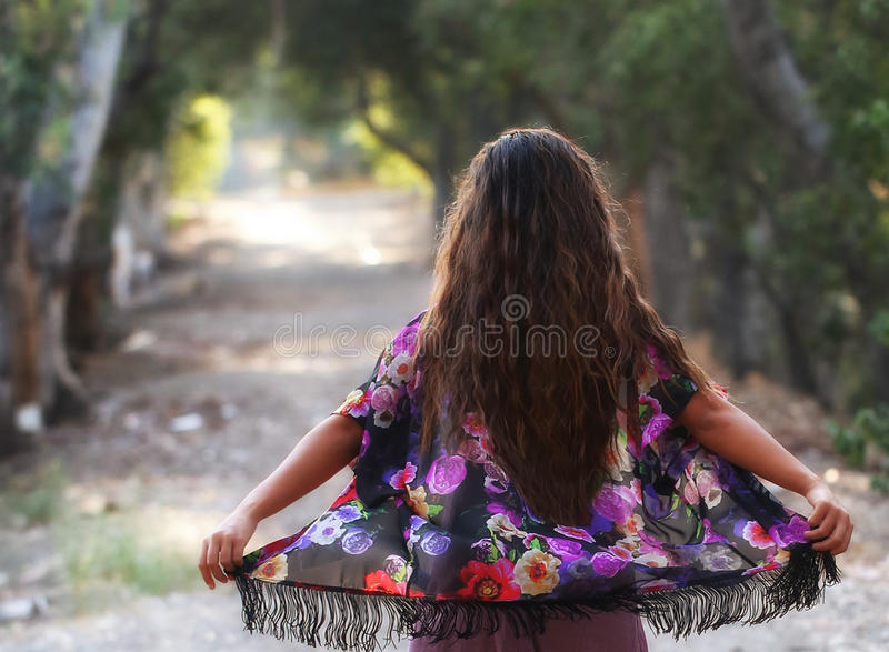 Girl enjoying the breeze. A long haired girl, standing against a breeze, holding her flowered kimono out to feel the air stock images