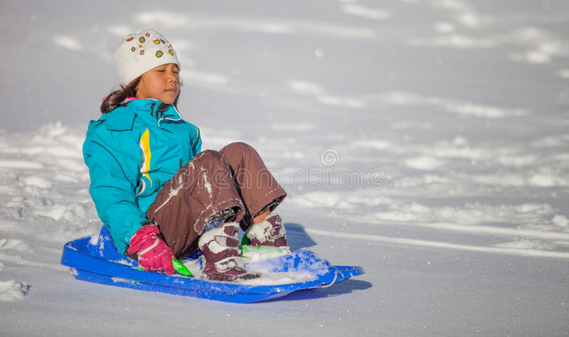Girl Enjoying A Downhill Sled Ride III. A little girl enjoying a sled ride down the hill in St Cergue, Switzerland stock images