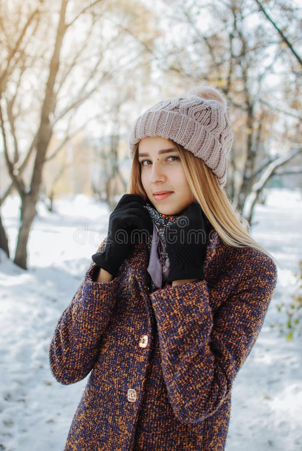 Girl enjoying first snow. Girl in hat and coat enjoying first snow in park stock photo