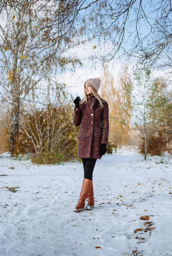 Girl enjoying first snow. Girl in hat and coat enjoying first snow in park royalty free stock image