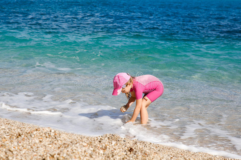 Girl enjoying free time on the beach. Collecting pebbles and shells, dressed in wetsuit and a hat for sun protection. Family and children on vacation, summer royalty free stock image