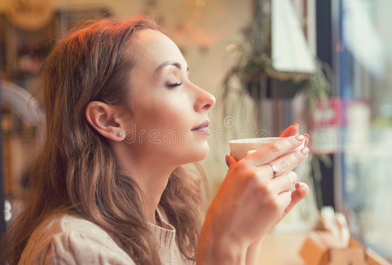 Girl enjoying fresh coffee in cafeteria royalty free stock photography