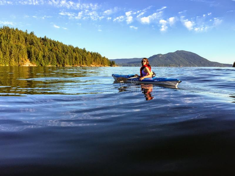 A girl enjoying kayaking on the beautiful and calm ocean waters of Howe Sound, off of Gambier Island, British Columbia, Canada. royalty free stock photography