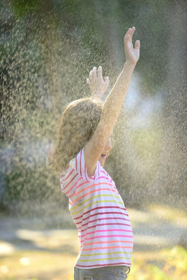 Girl enjoying the light summer rain. royalty free stock photography