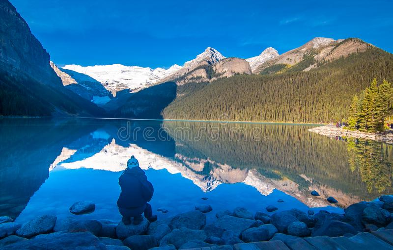Girl enjoying the reflection of snowy mountain and evergreen tree in the water of lake Louise. Banff national park, Alberta, Canada stock photos