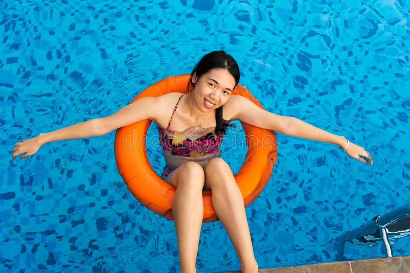 Girl enjoying at the swimming pool. Floating on water, woman, summer, vacation, female, person, asian, chinese, lounger, relax, tire, sunny, leisure, young, sea royalty free stock images