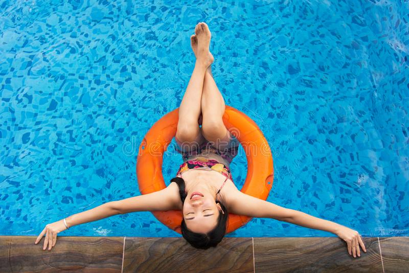 Girl enjoying at the swimming pool. Floating on water, woman, top, summer, vacation, female, person, asian, chinese, lounger, relax, tire, sunny, leisure, young royalty free stock photos