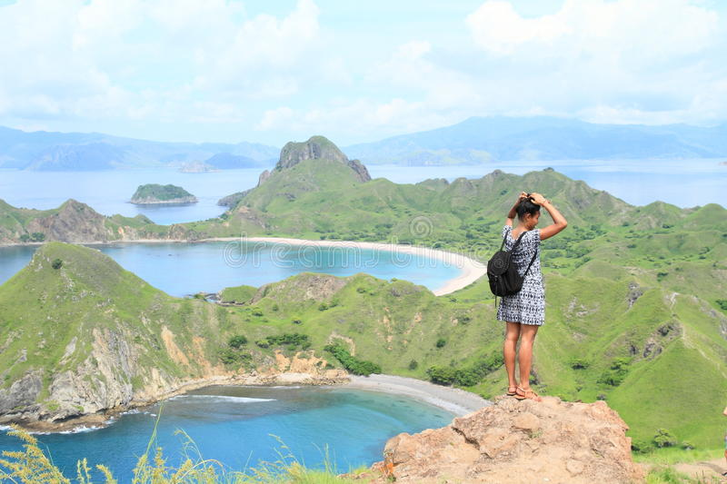 Girl enjoying view on Padar Island. Papuan girl - young woman standing on viewpoint and enjoying view on famous bays on Padar Island with rocky mountains and royalty free stock photos