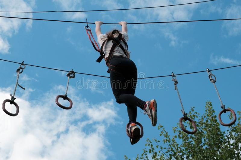 A girl enjoys climbing in the ropes course adventure. Climbing high wire park. Copy space for your text. stock photography