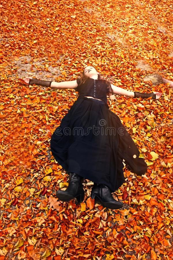 Girl enjoys the last sunbeams in orange autumn. Teenage girl dressed in gothic style enjoys the last sun in autumn forest. She lies on the orange foliage stock photos
