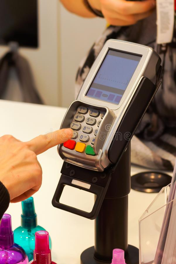 The girl enters the pin code on the terminal to pay for purchases in store stock images
