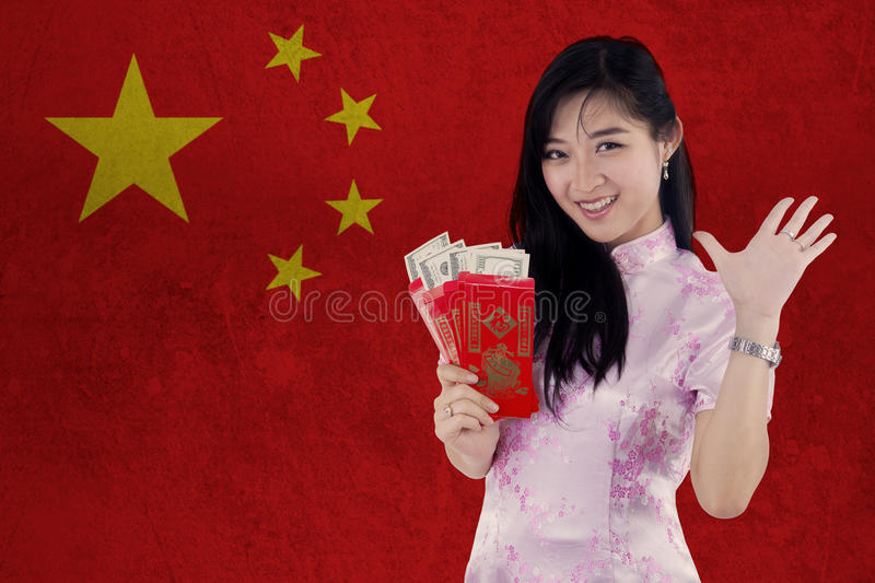 Girl with envelope celebrate Chinese new year. Image of happy young woman celebrate Chinese new year while wearing cheongsam clothes and holding envelope with stock photo