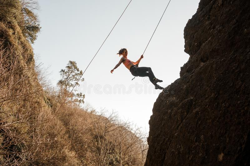 Girl equipped with a rope abseiling on the sloping rock royalty free stock photos
