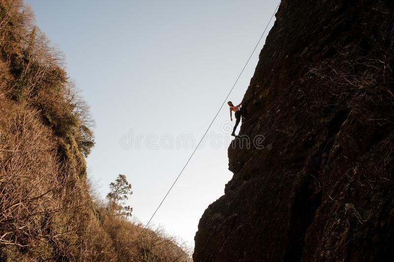 Girl equipped with a rope climbing on the sloping rock and looking back royalty free stock images