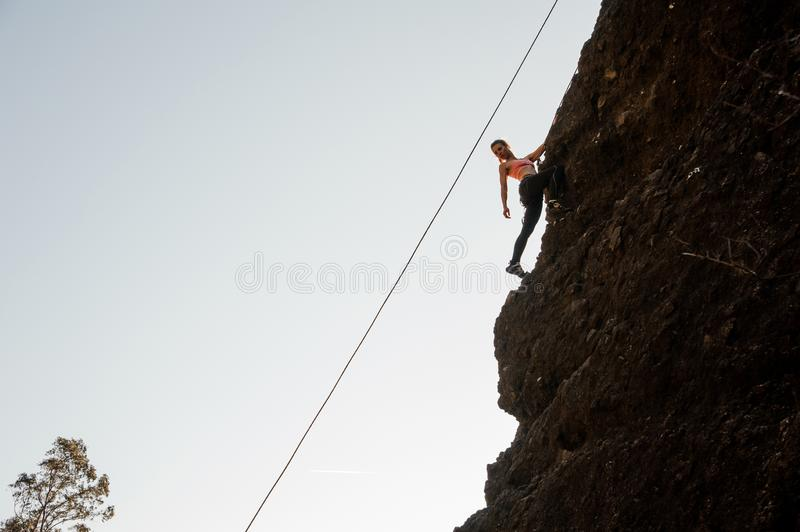 Girl equipped with a rope climbing on the sloping rock and looking down royalty free stock image