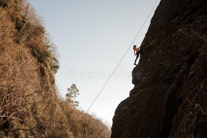 Girl equipped with a rope climbing on the sloping rock and looking up stock photography