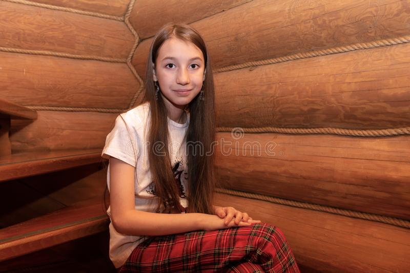 A girl of European appearance with long hair is sitting on a wooden staircase in a log house. stock photography