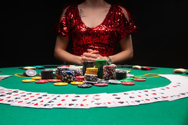 A girl in an evening red dress plays with cards in a casino raising the stacks with croupier chips. Gaming business casinos, night. Clubs stock photography