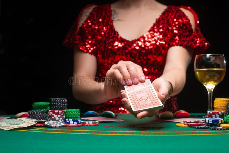 A girl in an evening red dress plays in a casino and draws cards. Gambling business casino royalty free stock photography