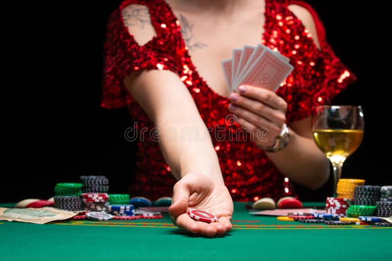 A girl in an evening red dress plays in a casino, holds a chip for a croupier. Gambling business casino.  royalty free stock photography