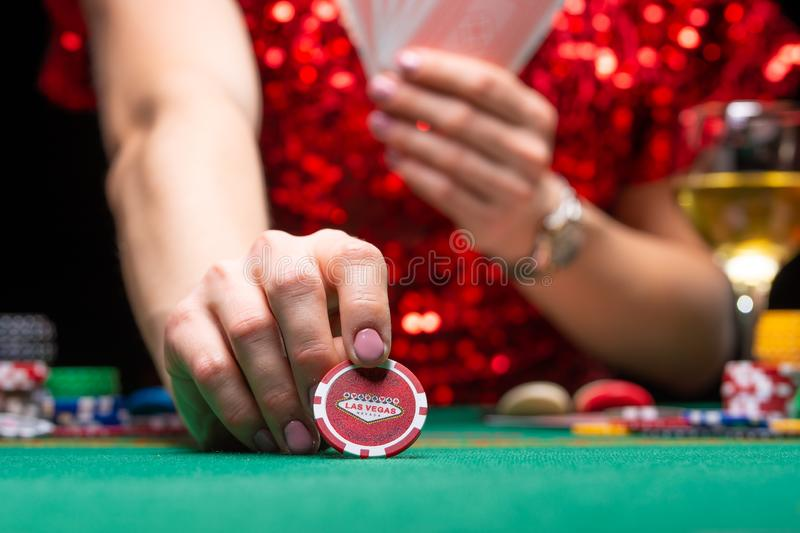 A girl in an evening red dress plays in a casino, holds a chip for a croupier. Gambling business casino.  stock photos