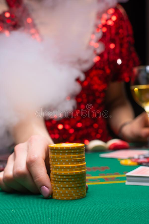 A girl in an evening red dress plays in a casino raising the stacks with croupier chips. Gaming business casinos, night clubs.  royalty free stock photography