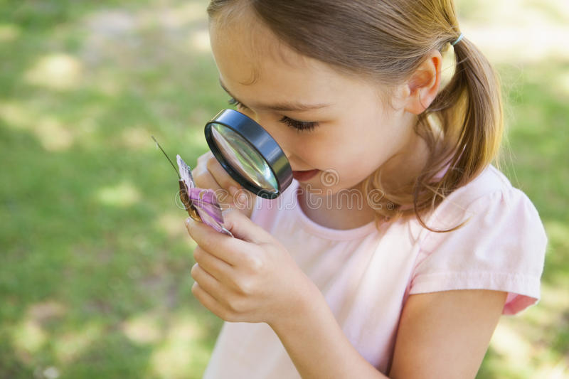 Girl examining butterfly with magnifying glass at park stock images