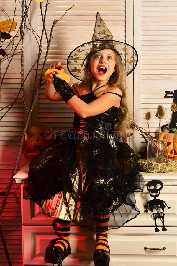 Girl with excited face on spooky carnival room background. Little witch with Halloween decor. Halloween party and celebration concept. Kid in witch hat and stock photo