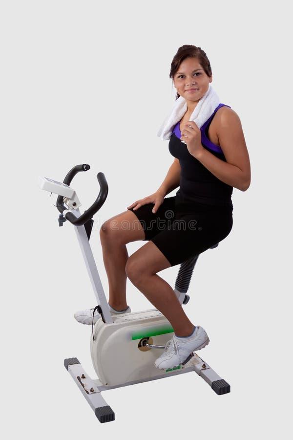 Girl on exercise bike stock photo