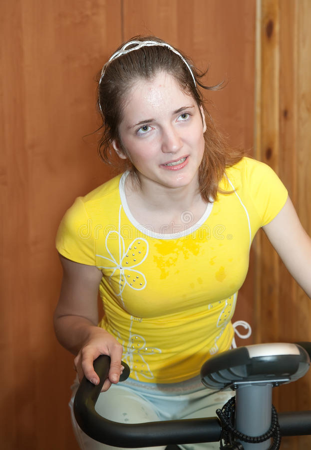 Girl exercising at exercycle royalty free stock photo