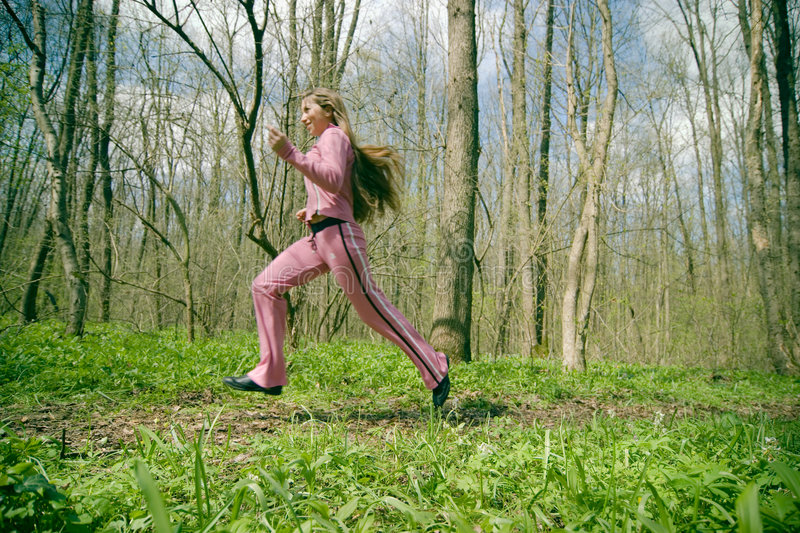 Girl exercising in the forest stock images