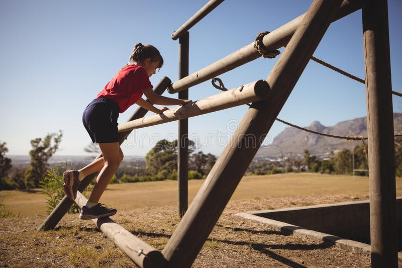 Girl exercising on outdoor equipment during obstacle course royalty free stock image