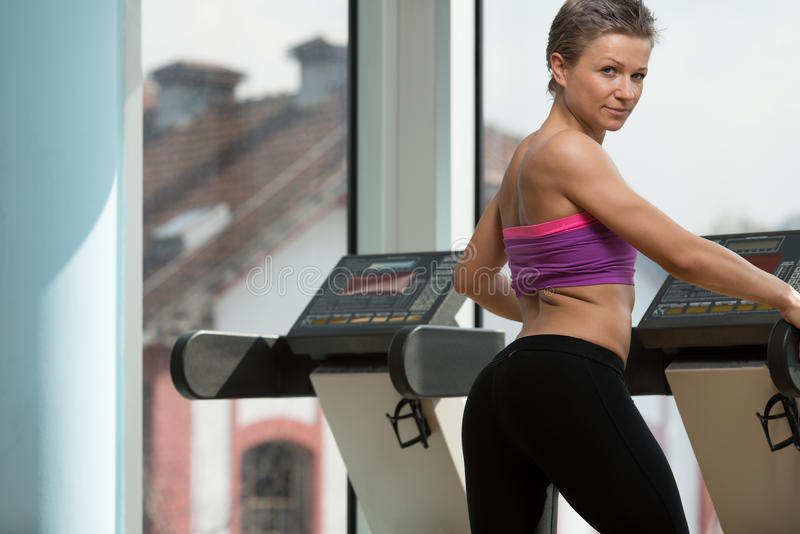 Girl Exercising On Step Machine In Fitness Club. Young Attractive Girl Exercise In Fitness Club On Step Machine royalty free stock photography