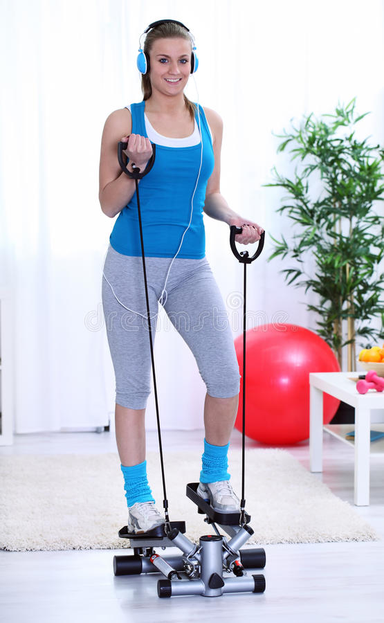 Girl exercising on stepper trainer. Young woman exercising on stepper trainer at home royalty free stock photo