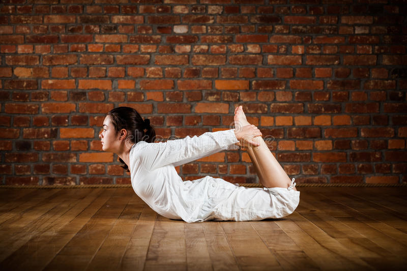Girl exercising yoga against brick wall royalty free stock images