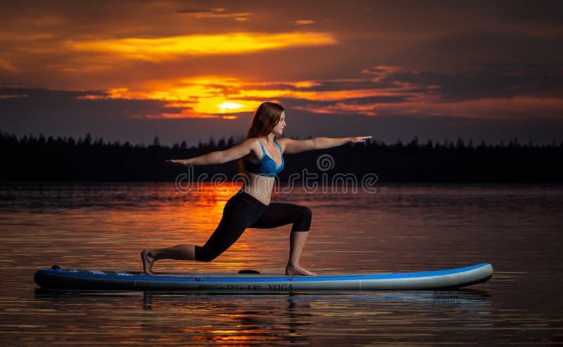 Girl exercising yoga on paddleboard in the sunset on scenic lake Velke Darko stock photo