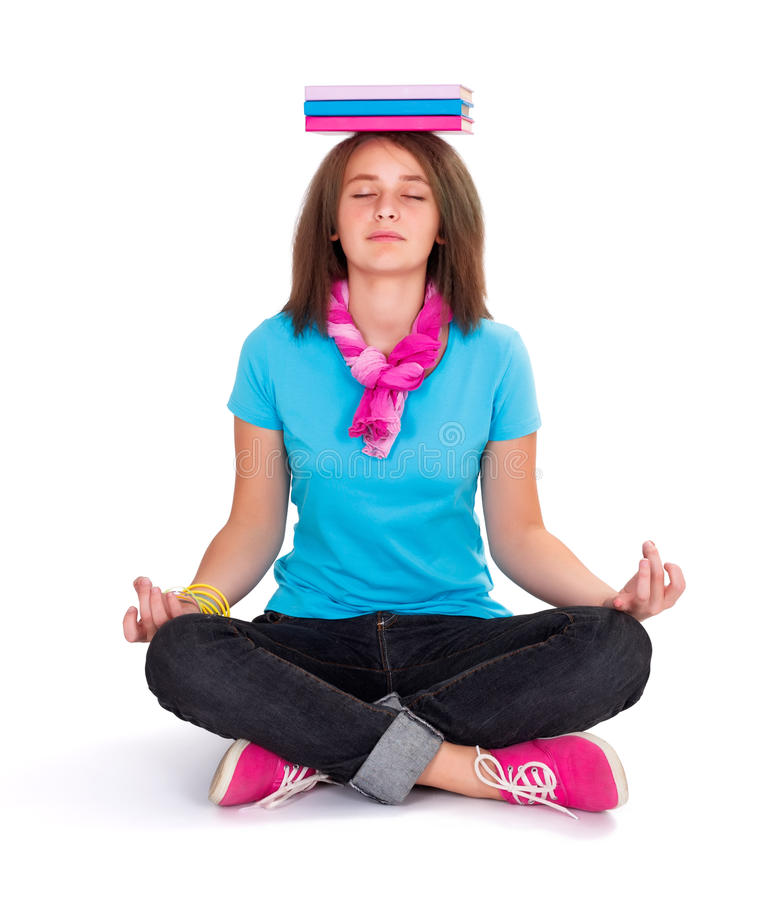 Girl exercising Yoga. Pretty teenage schoolgirl in lotus position exercising meditation with books on the head stock photos