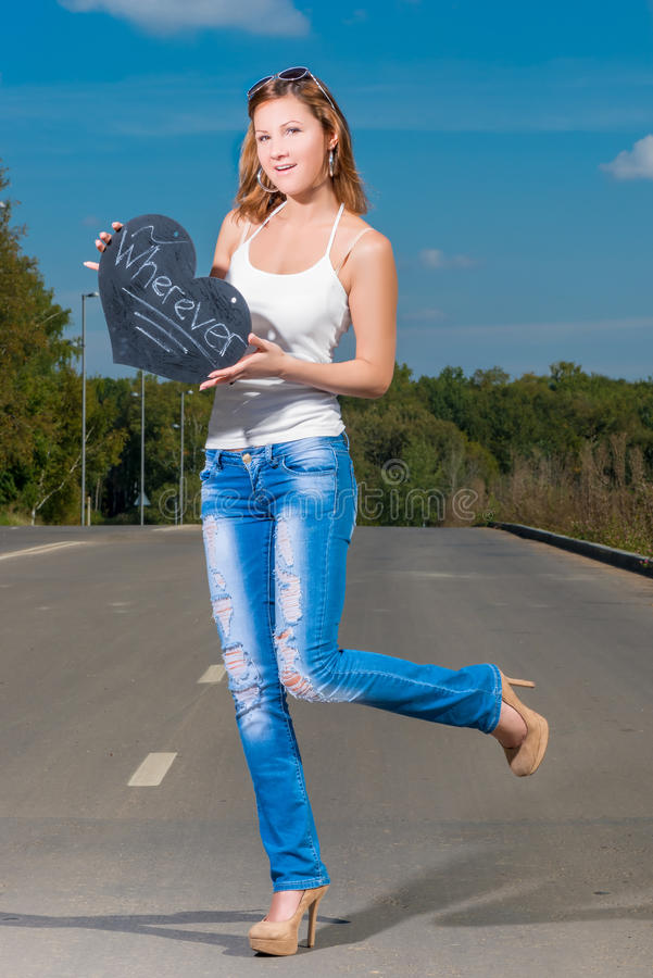 Girl in expectation of vehicle, hitchhiking. Girl in expectation of a vehicle, hitchhiking royalty free stock image