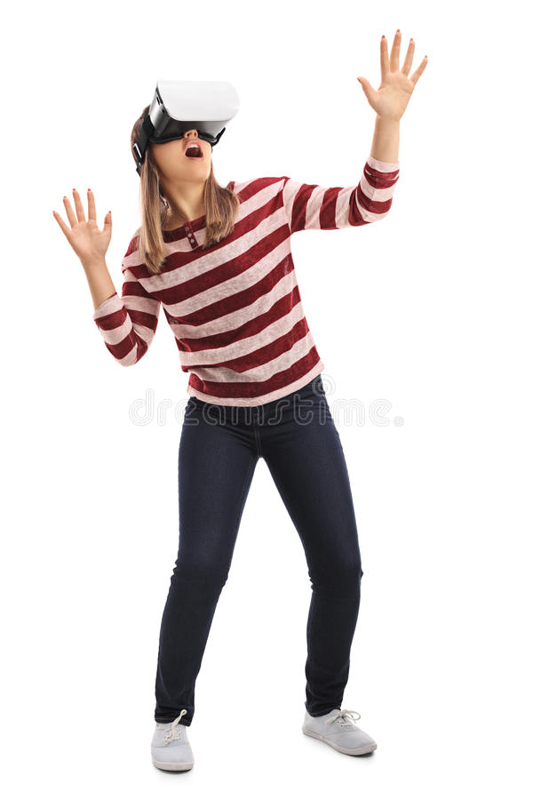 Girl experiencing virtual reality through a VR headset. Full length portrait of a girl experiencing virtual reality through a VR headset isolated on white royalty free stock image