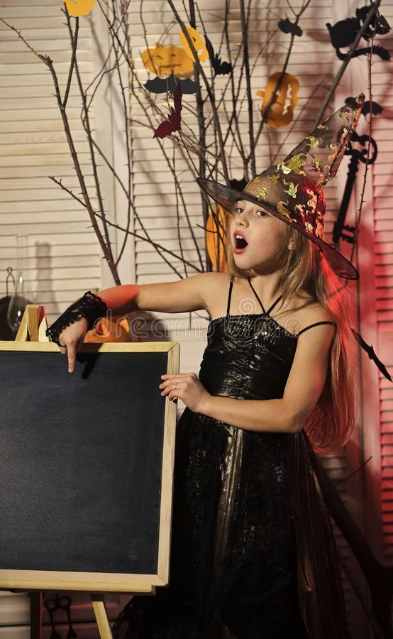 Girl with explaining face on spooky carnival room background. Little witch with Halloween decor. Kid in witch hat and costume points at blackboard. Halloween royalty free stock images