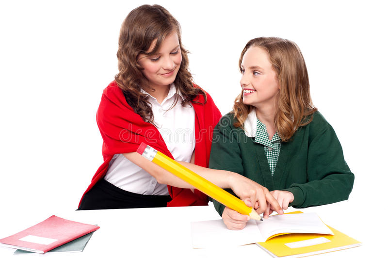 Girl explaining solution to her friend. And helping her resolve question royalty free stock photos