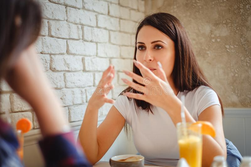 Girl explaining something to her friend in the restaurant royalty free stock photo
