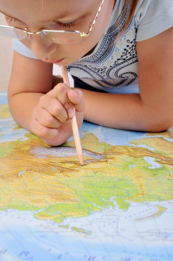Girl exploring the map of Eurasia. Girl exploring the geographic map of Eurasia royalty free stock image